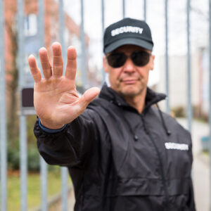 Security Guard Making Stop Gesture In Front Of Gate